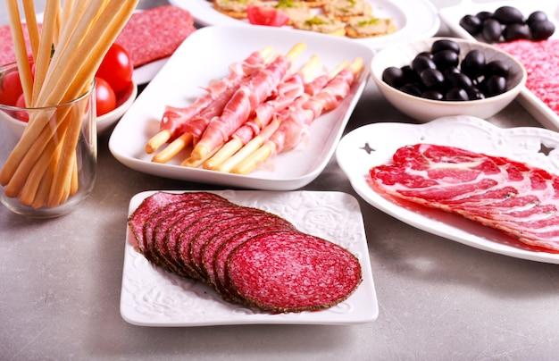 Mélange de produits carnés et apéritifs servis sur table