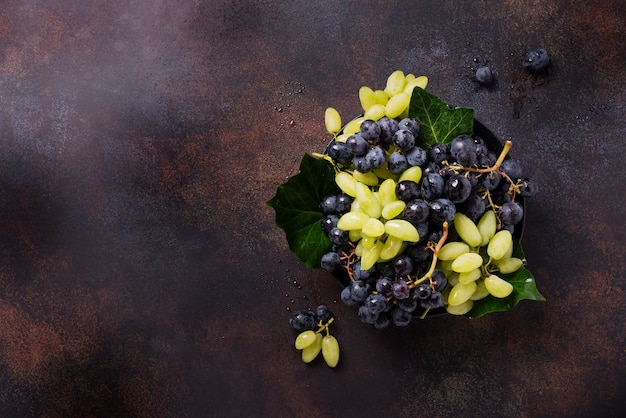 Mélange de raisin blanc et noir sur l'obscurité