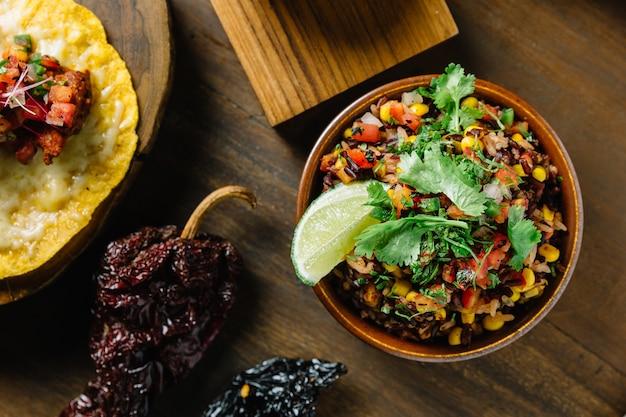 Mélange de riz mexicain authentique (arroz rojo) avec des baies de riz, des tomates et du maïs.