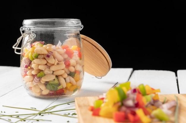 Mélange de salade de haricots dans un bocal fond noir