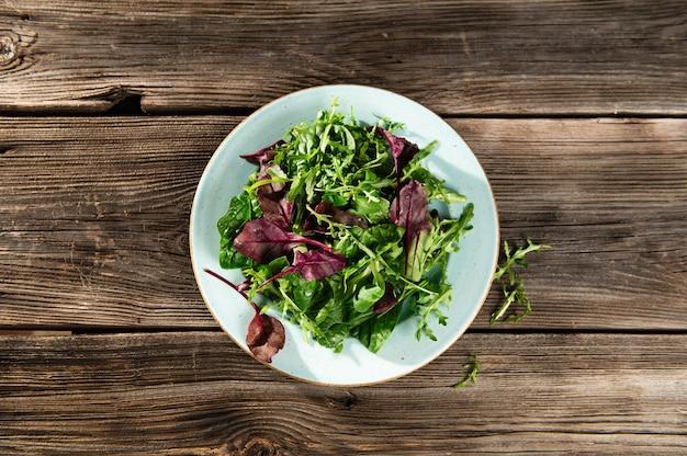 Mélange de salade d'herbes fraîches dans une assiette sur fond de bois