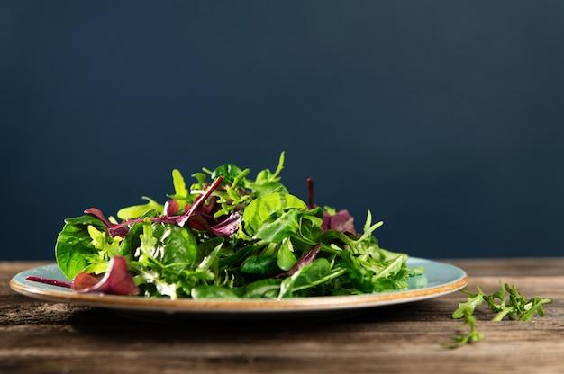 Mélange de salade d'herbes fraîches, de roquette, de bette à carde et d'épinards sur une table en bois et un fond bleu foncé