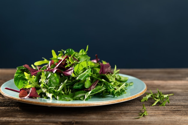 Mélange de salade d'herbes fraîches, de roquette, de blettes et d'épinards en tarenle sur fond de bois