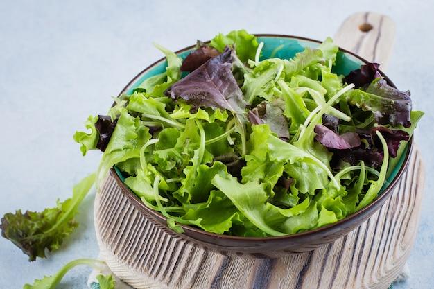 Mélange de salade verte dans un bol et deux citrons sur une planche de bois sur la table. concept alimentaire de régime alimentaire sain. vue de dessus, espace de copie