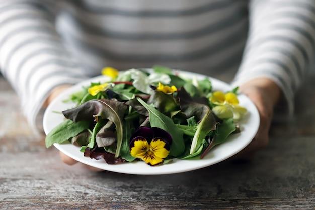 Mélange de salades avec des fleurs sur une assiette blanche tenue par une fille