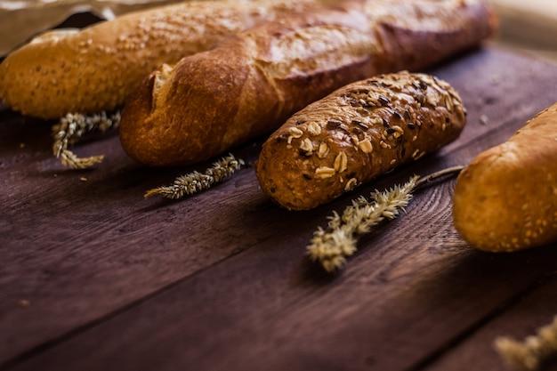 Mélange de sortes de baguettes sur une table en bois. produits de boulangerie.