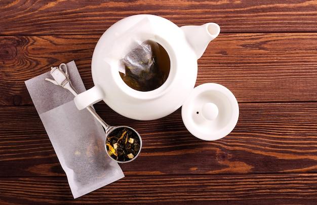 Mélange de thé fait maison en sachets de thé, sur fond de bois