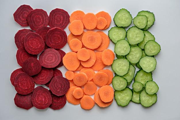 Mélange de tranches de légumes betterave, carotte, concombre sur fond blanc, composition végétale