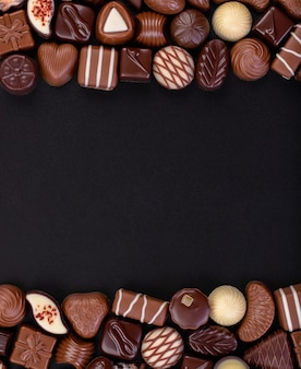 Mélanger les bonbons au chocolat et autres douceurs sur fond de tableau noir, cadre de nourriture sucrée