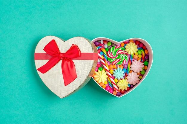 Mélanger les bonbons au chocolat se trouvent en forme de boîte cadeau de coeur sur fond coloré