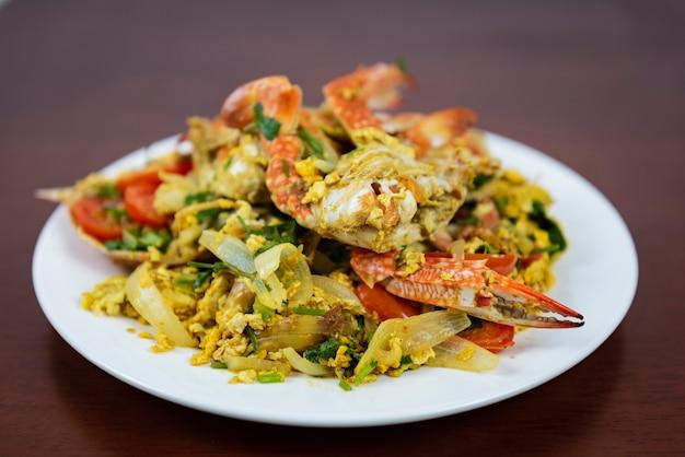 Mélanger du crabe frit avec de la poudre de curry, closeup, cuisine thaïlandaise sur fond en bois