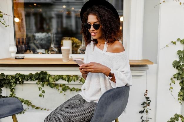 Mélanger la femme de course en tenue décontractée élégante se détendre en plein air dans le café de la ville, boire du café et discuter par téléphone mobile. porter des accessoires et des lunettes de soleil tendance.