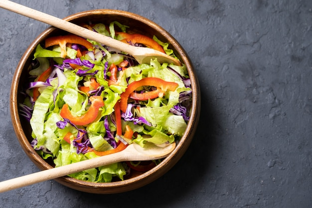Mélanger les feuilles de salade dans un bol noir sur un fond d'ardoise sombre, de pierre ou de béton.