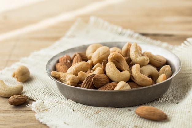 Mélanger le fond et le papier peint des noix et des fruits secs. vu en vue de dessus de mélanger les noix et les fruits secs dans le bol et la cuillère en bois décorée de noix et de feuilles vertes sur du bois blanc en arrière-plan.
