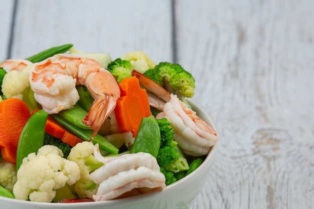 Mélanger les légumes frits avec les crevettes.
