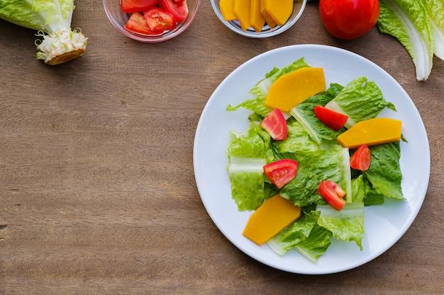 Mélanger les légumes à salade dans un plat blanc, végétalien
