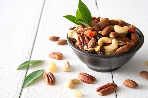 Mélanger les noix et les fruits secs dans le bol mettre sur le bois peint en blanc.