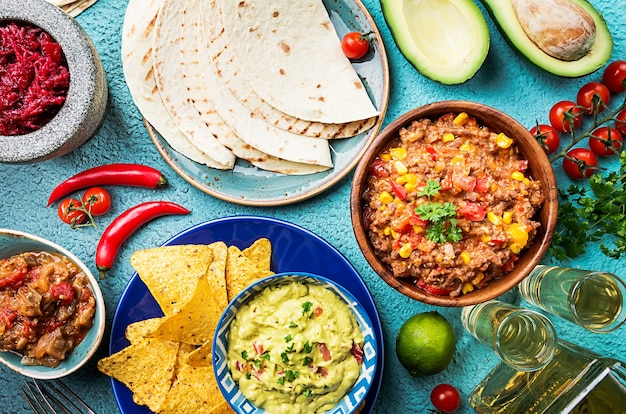 Mélanger la nourriture mexicaine nachos, fajitas, tortilla, guacamole et sauces et ingrédients sur la surface bleue. vue de dessus