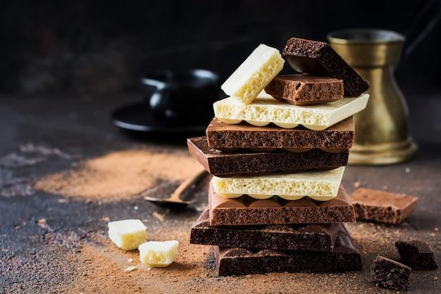 Mélanger la pile de chocolat aéré poreux amer, laiteux et blanc sur une vieille surface sombre. mise au point sélective.