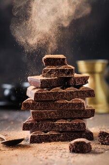 Mélanger pile de chocolat aéré poreux amer et laiteux avec nuage de cacao sur une vieille surface sombre