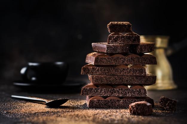 Mélanger la pile de chocolat aéré poreux amer et laiteux sur une vieille surface sombre
