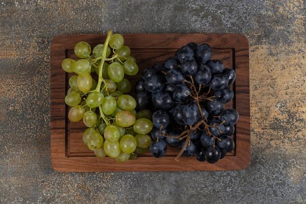 Mélanger les raisins frais sur une planche de bois.
