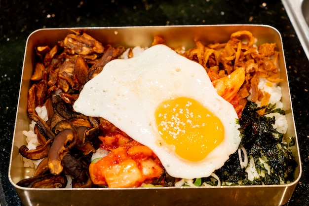 Mélanger le riz avec l'oeuf au plat