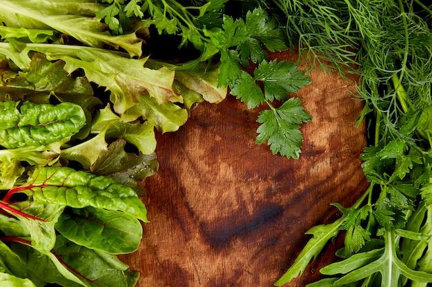 Mélanger la salade de feuilles sur une planche à découper en bois,