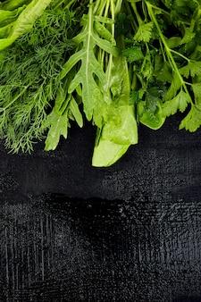 Mélanger la salade de feuilles sur une table noire.