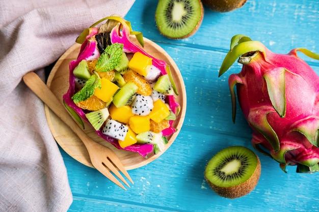 Mélanger la salade de fruits tropicaux servie dans un demi-fruit du dragon sur une table en bois