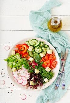 Mélanger la salade de légumes frais et d'herbes vertes. mise à plat. vue de dessus