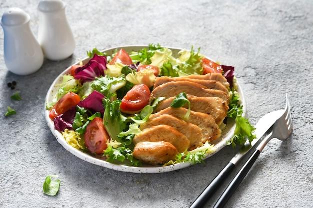 Mélanger la salade avec les tomates et le filet de poulet dans une assiette.