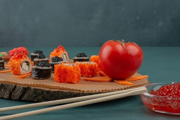 Mélanger les sushis et le caviar rouge sur une surface bleue.
