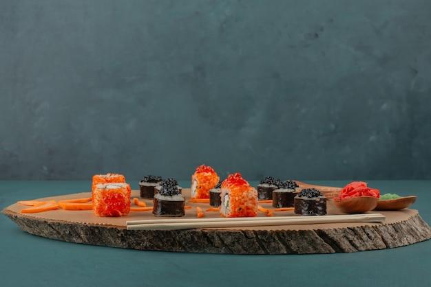 Mélanger les sushis et les cuillères de gingembre mariné et de wasabi sur une planche de bois.