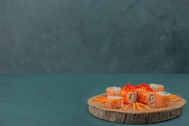 Mélanger les sushis avec des tranches de carottes sur une planche de bois.