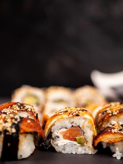 Mélanger une variété de rouleaux de sushi sur fond de pierre noire en studio