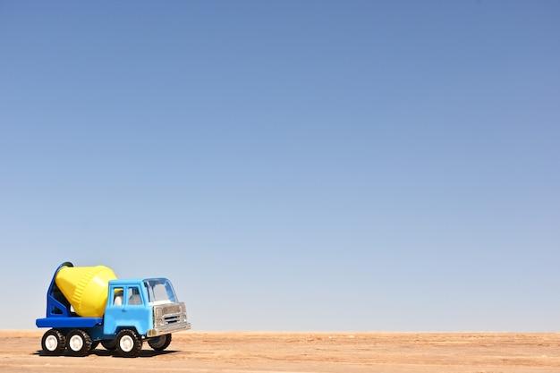 Mélangeur de camion jouet collection à l'échelle plancher en bois et fond de ciel bleu macro