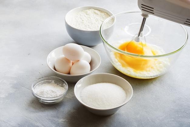 Mélangeur fouettant des œufs dans un bol en verre et des ingrédients pour créer un gâteau