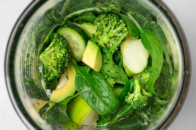 Mélangeur avec des ingrédients pour cuisiner un smoothie vert détox sain. épinards, brocoli, avocat, pomme et concombre. vue de dessus. concept de saine alimentation et régime