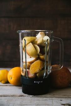 Mélangeur plein de mélange de fruits sur une table en bois