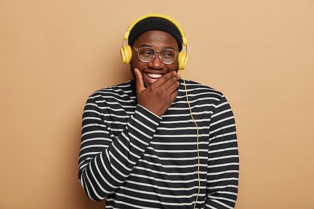 Meloman mâle joyeux avec une expression heureuse, rit de la chanson drôle, de la musique en streaming optimiste, tient le menton, sourit largement