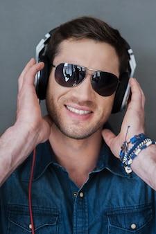 Mélomane insouciant. jeune homme gai dans des écouteurs souriant et regardant la caméra