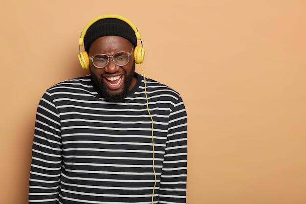 Le mélomane rit joyeusement tout en écoutant la piste audio dans des écouteurs stéréo, porte de grandes lunettes optiques et un pull rayé