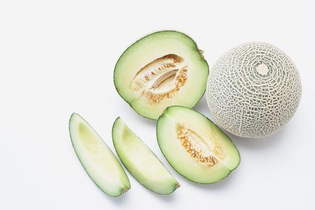 Melon cantaloup hami frais avec des tranches isolés sur fond blanc.