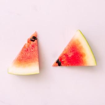 Melon d'eau brillant en tranches placé sur une surface rose