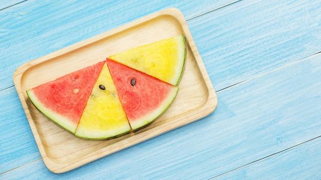 Melon d'eau rouge et jaune sur une assiette et une table en bois bleue.