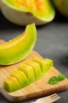 Melon frais, coupé en morceaux, mis sur une planche à découper en bois