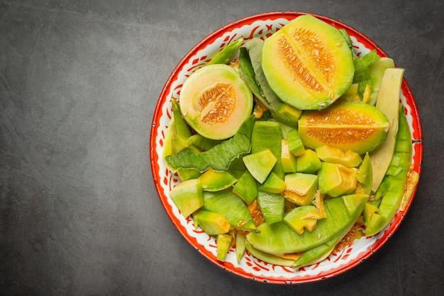 Melon frais, coupé en morceaux, mis sur le plateau