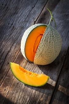 Melon frais en tranches sur une planche de bois. texture orange et jus de fruits au goût.