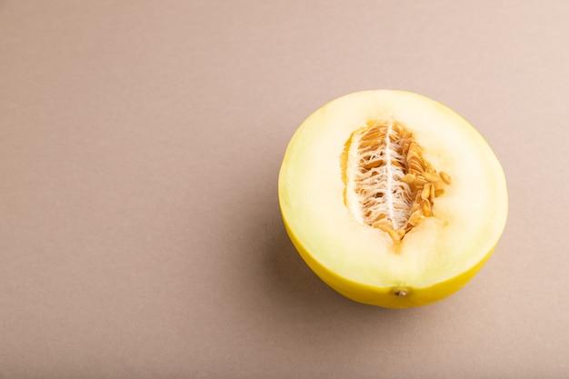 Melon jaune mûr tranché sur fond pastel marron. vue latérale, copiez l'espace. récolte, santé des femmes,